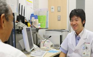 定期検査でがん細胞が小さくなっていると聞く大西さん(仮名、写真手前) =福岡市の九州大学病院