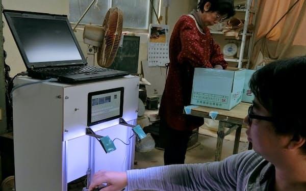 キュウリを自動で仕分けるAIを開発した小池さん。奥は手作業で仕分ける小池さんの母(静岡県湖西市)
