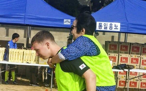 脱北者の運動会で若い米兵がおばあさんをおんぶしている