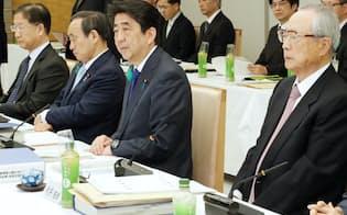 有識者会議の今井座長(右端)から最終報告を受け取り、あいさつする安倍首相(21日、首相官邸)