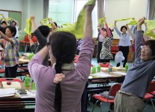 研修会でバンダナを使った体操を習う保健補導員ら