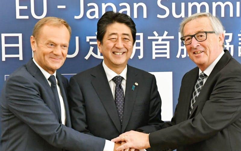 EUのトゥスク大統領(左)、ユンケル欧州委員長(右)と握手を交わす安倍首相(6日、ブリュッセル)=代表撮影・共同