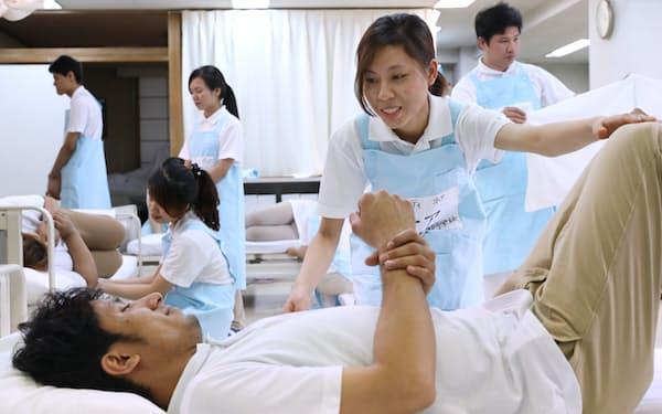 シーツ交換など介護の実技授業を受ける留学生ら(東京都内の専門学校)