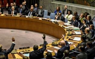 11日、国連安保理で採決する各国国連大使ら(ニューヨーク)=ロイター