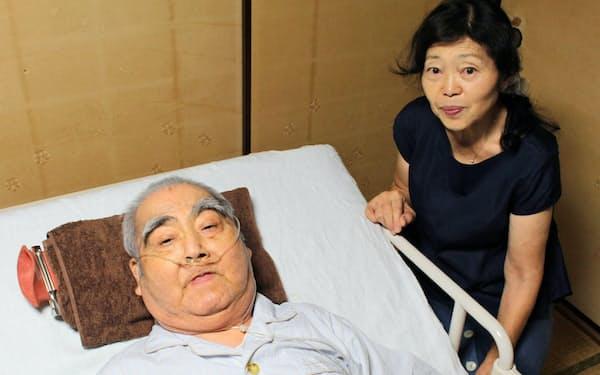 在宅酸素療法をする西谷さん(左)と介護する妻の紀子さん