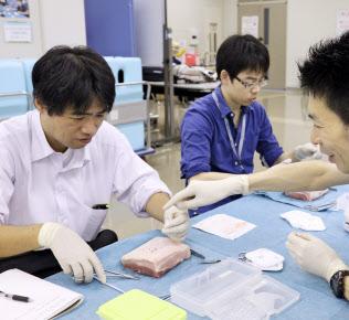 研修医(中央)と並んで豚の皮を使った皮膚縫合を体験する記者(左)(9月16日、横浜市立大病院)