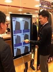 店内の大型タッチパネルを使い、スーツをネット通販サイトで注文する(東京都調布市の店舗)