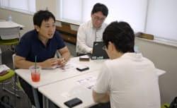 ベンチャーキャピタル関係者と面談するネクストイノベーションの石井社長(左)(7月、大阪市)