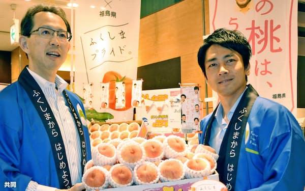 攻めの農家を応援する(福島県の内堀知事とともに福島産の桃をPRする小泉氏(右))=共同