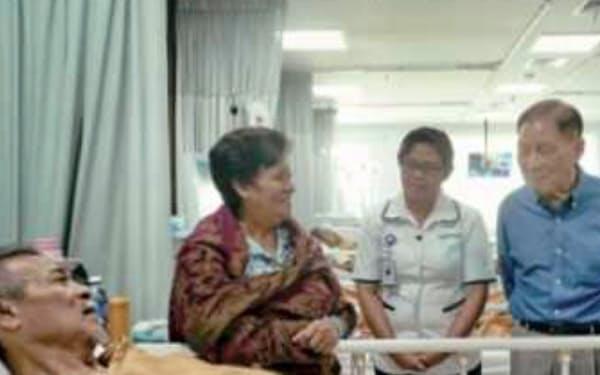 系列病院で患者を見舞う筆者(右)(シロアム病院)