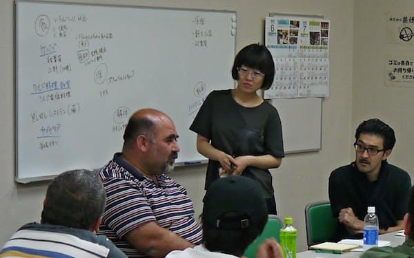 ワークショップでクルド人男性(左から2人目)にインタビューする高山明(右)