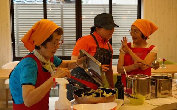 高齢者らがスタッフに確認しながら料理を作る(東京都目黒区のなないろクッキングスタジオ自由が丘)
