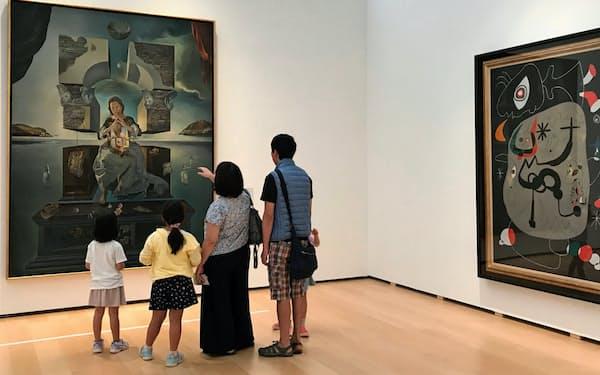 福岡市美術館のコレクション展「モダンアート再訪」でダリの大作を鑑賞する来場者。右はミロの作品「ゴシック聖堂でオルガン演奏を聞いている踊り子」(神奈川県横須賀市の横須賀美術館)