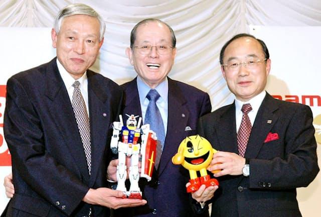 会見で互いのキャラクターを手にするナムコの高木副会長(左)と中村会長(中)、バンダイの高須社長(2005年5月)