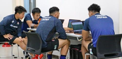 パソコンを見ながら自主的にミーティングをする日本代表の流(左から2人目)ら=日本ラグビー協会提供