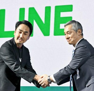 記者会見で握手するLINEの出沢社長(左)とみずほフィナンシャルグループの岡部副社長(27日、東京都渋谷区)