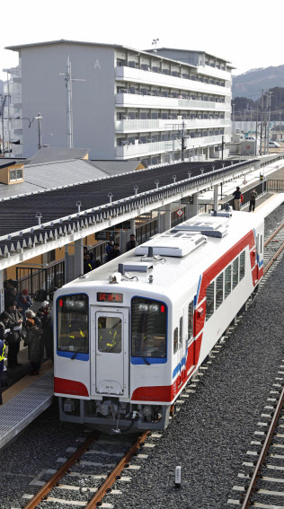 JR山田線の試運転で、陸中山田駅に到着した車両。奥は災害公営住宅(28日)