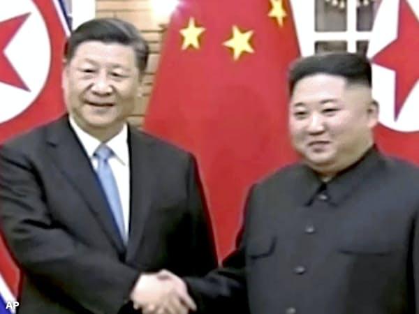 中国国営中央テレビが20日放映した、平壌で握手する中国の習主席(左)と北朝鮮の金委員長=AP
