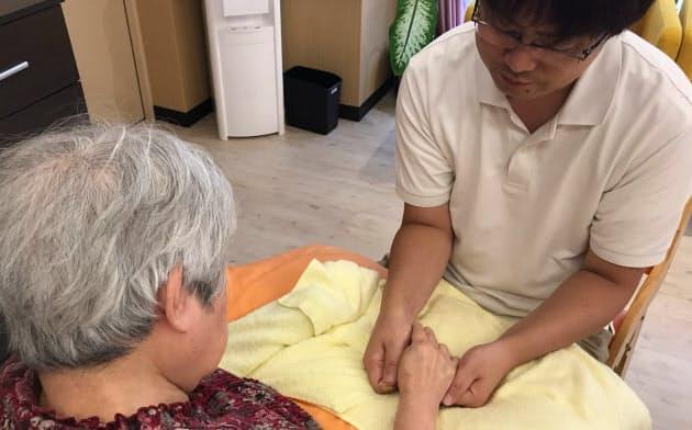 手を包み込むようにしてケアをする施設長の戸倉英人さん(東京都江戸川区)