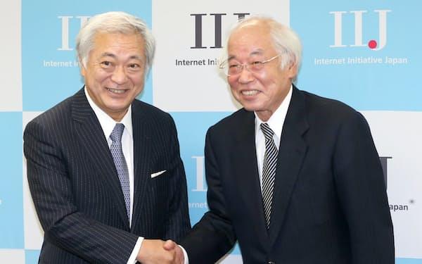 記者会見で握手するIIJの勝栄二郎特別顧問(左)と筆者