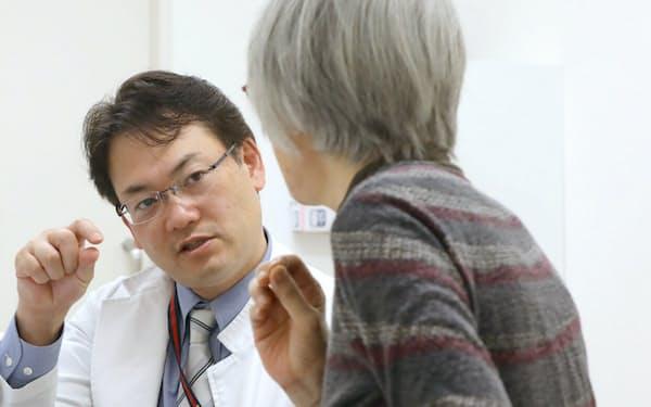 がん遺伝子外来で医師に問診を受けるがん患者(右)(東京都新宿区の慶応義塾大学病院)
