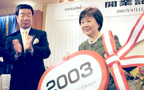 「スイスホテル南海大阪」開業時、ラッフルズのジェニー・チュア会長(当時、右)に鍵の模型を渡す(2003年)