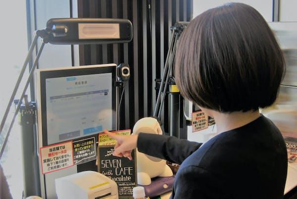 顔認証システムを使い無人のレジで購入した商品を精算する(東京都港区のセブンイレブン三田国際ビル20F店)