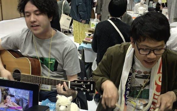 イベントで架空のCMソングを披露する筆者(左)と相棒のタニケン