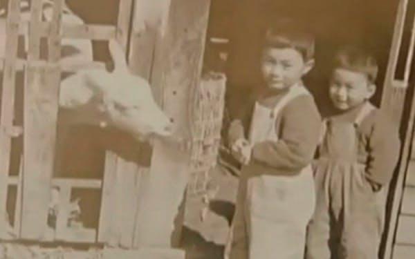 実家のヤギ小屋の前で弟(右)と