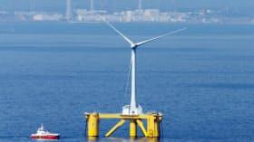 洋上風力産業の推進などを目指す点は評価できる(福島県沖の浮体式洋上風力発電所の風車。後方は福島第1原発、2014年3月)
