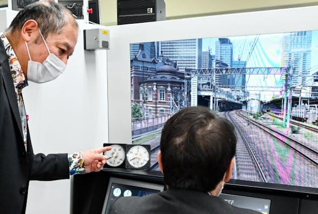 音楽館の向谷実社長(左)に運転士訓練用「トレインシミュレータ」の操作を教わりながら体験する記者(東京都品川区)=佐藤 圭一郎撮影