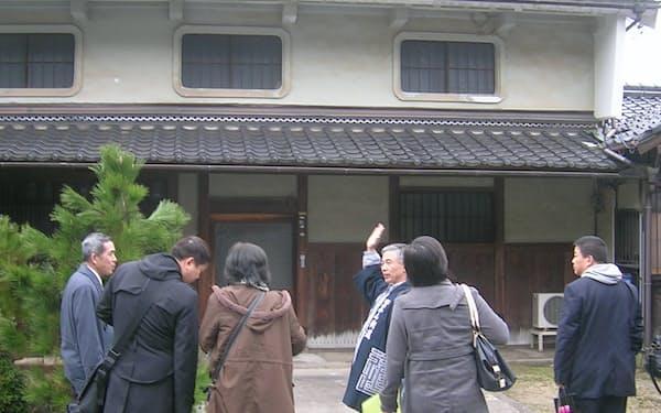 「ちりめん街道」沿いを案内する与謝野町語り部の会の青木順一会長(中央)