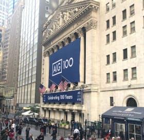 AIGもダイベストメントの波にさらされる(ニューヨーク証券取引所に掲げられた創立100周年を祝うバナー)=ロイター