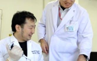 金沢大で開発機器の実験をする米田特任准教授(右)とメディカル・イノベーションコースで学ぶ米谷さん