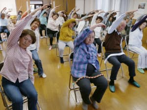 いすに座ったままでもできる体操をする高齢者(大阪府大東市)