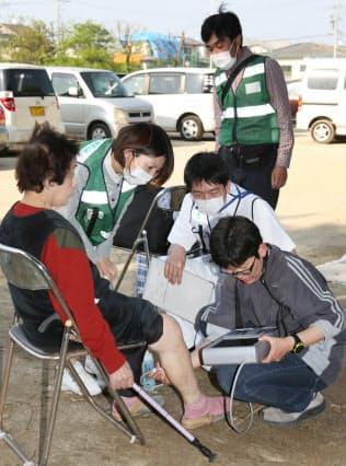 避難所の被災者にエコノミークラス症候群の診断をする熊本市民病院の医療チーム(19日、熊本県益城町)