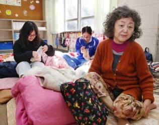 避難所になっている教室の床に敷いた毛布の上で足をさする女性(20日午前、熊本市北区の龍田小)