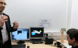VR実験設備。画面上の物体に触れると手に触感が伝わる。