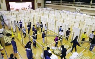 避難所の体育館に、簡易式の間仕切りを設営する人たち(24日午前、熊本市中央区の帯山西小学校)
