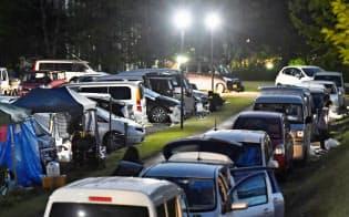 避難のため車中泊をする人々の車(熊本県益城町)=共同