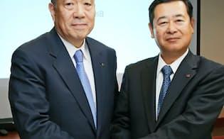 経営統合の発表会見で握手する東洋製缶GHDの中井社長(左)とホッカンHDの工藤社長(25日午後、東京都中央区)