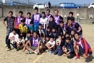 避難所で子どもたちとサッカー交流し、記念写真に納まるJ2熊本の巻誠一郎(前列左から4人目)ら=Jリーグ提供