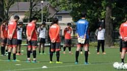 全体練習再開を前に黙とうするJ2熊本の選手たち(2日、熊本市)=共同