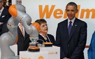 会場内で米独首脳にロボットの説明をするクーカのロイター社長(右)
