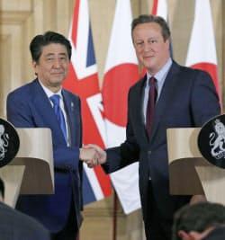共同記者会見を終え、握手する安倍首相(左)と英国のキャメロン首相(5日、ロンドン)=共同