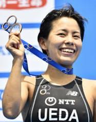 女子で3位になり、表彰台でメダルを手に笑顔の上田藍(14日、横浜市山下公園周辺特設コース)=共同