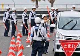 中部国際空港付近で車両検問をする警察官(25日午前、愛知県常滑市)