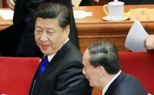 全国政治協商会議の開幕式を終えて習近平国家主席(左)に話しかける王岐山政治局常務委員(3月3日、北京の人民大会堂)=写真 小高顕