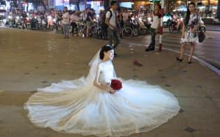 結婚式を終え、新婦が路上に座り込んで記念撮影