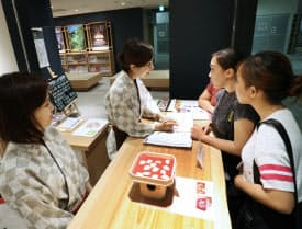京阪祇園四条駅の観光案内所で道を尋ねる外国人旅行客(京都市東山区)